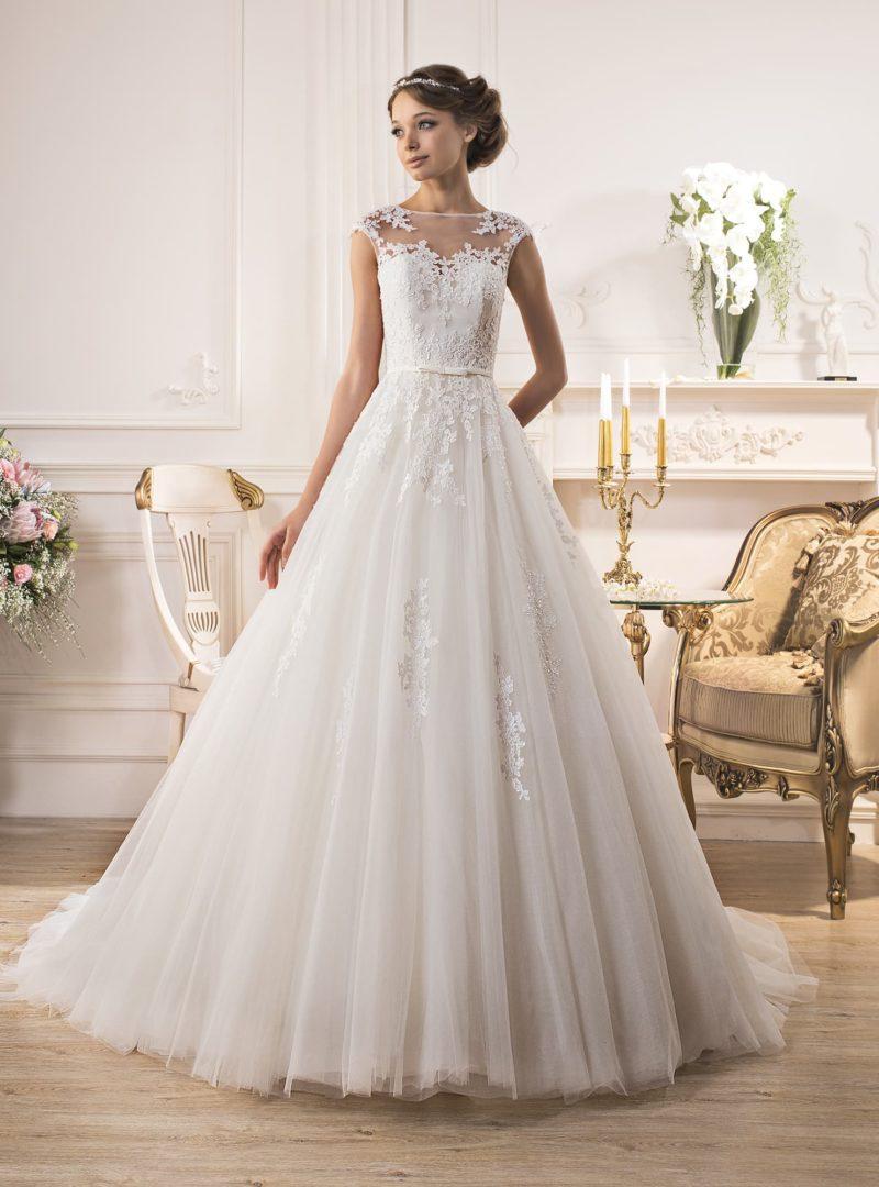 Пышное свадебное платье с закрытым лифом, украшенным ажурными аппликациями.