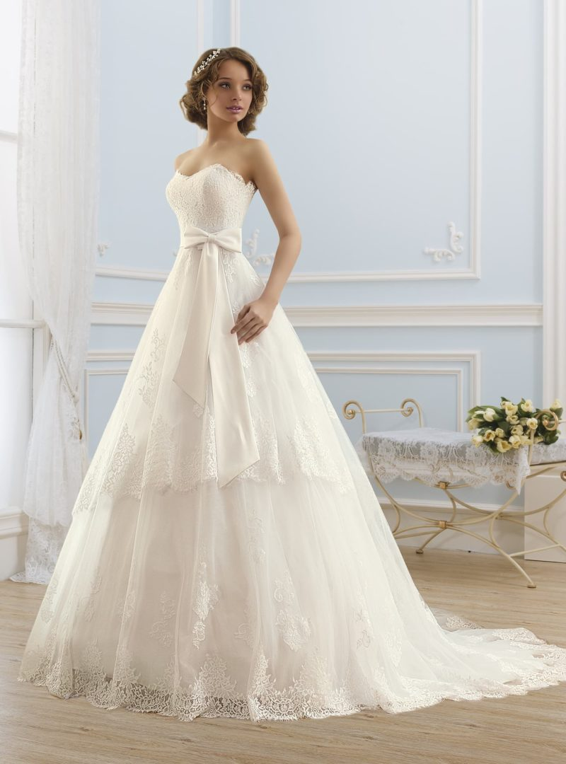 Пышное свадебное платье с многоярусной юбкой и широким поясом с бантом.
