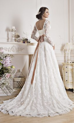 Кружевное свадебное платье силуэта с длинным рукавом и широким поясом.