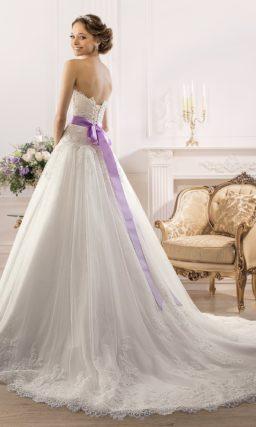 Роскошное свадебное платье с пышной юбкой со шлейфом и атласным поясом лилового цвета.