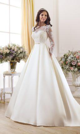 Свадебное платье силуэта «принцесса» с узким поясом и длинными полупрозрачными рукавами.