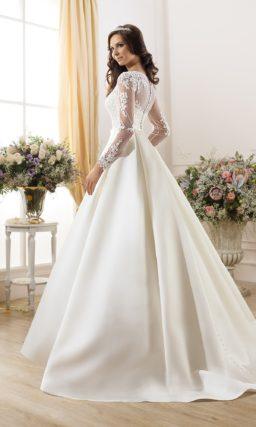 Свадебное платье с узким поясом и длинными полупрозрачными рукавами.