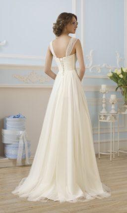 Прямое свадебное платье с драпировками на юбке и полупрозрачными бретелями.