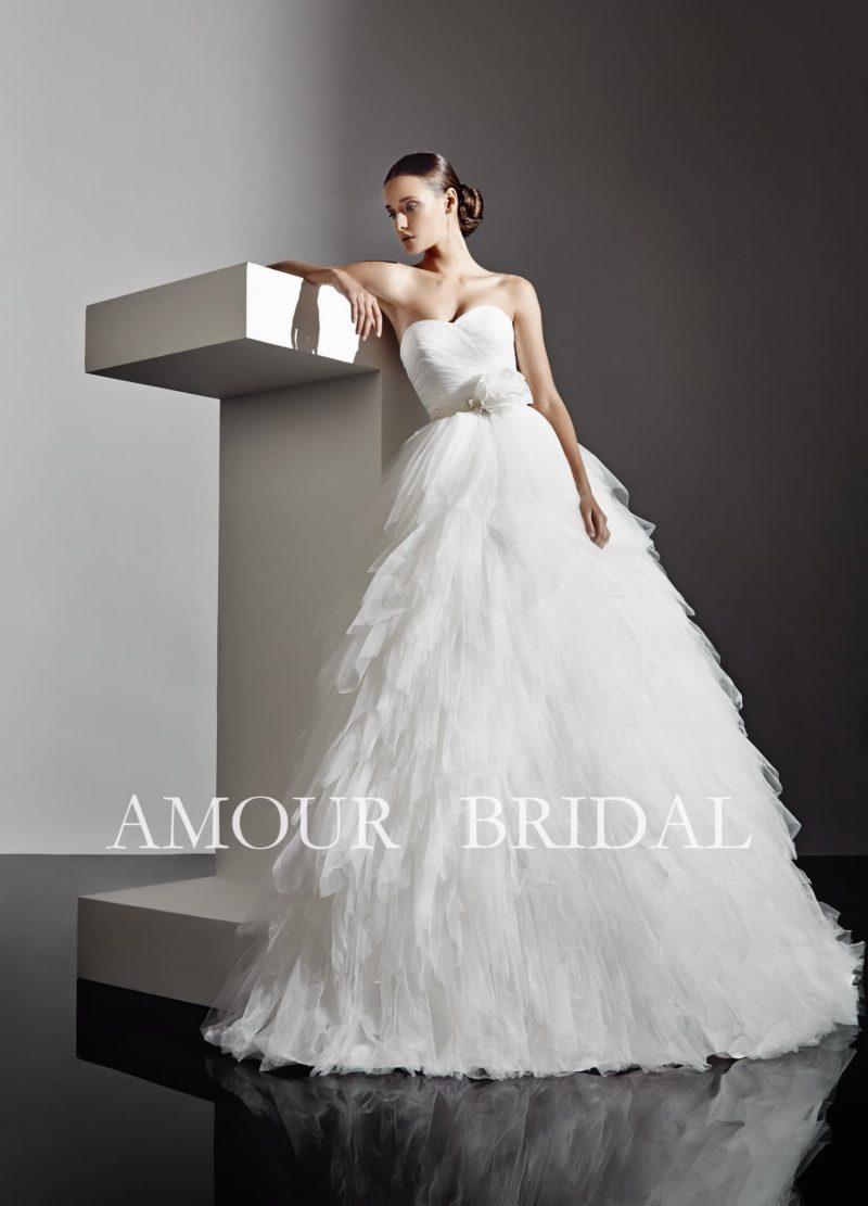 Пышное свадебное платье с драпировками на корсете по всей юбке покрыто оборками.