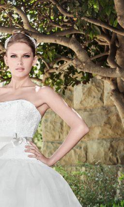 Свадебное платье с открытым лифом прямого кроя и многоуровневой юбкой с кружевом.