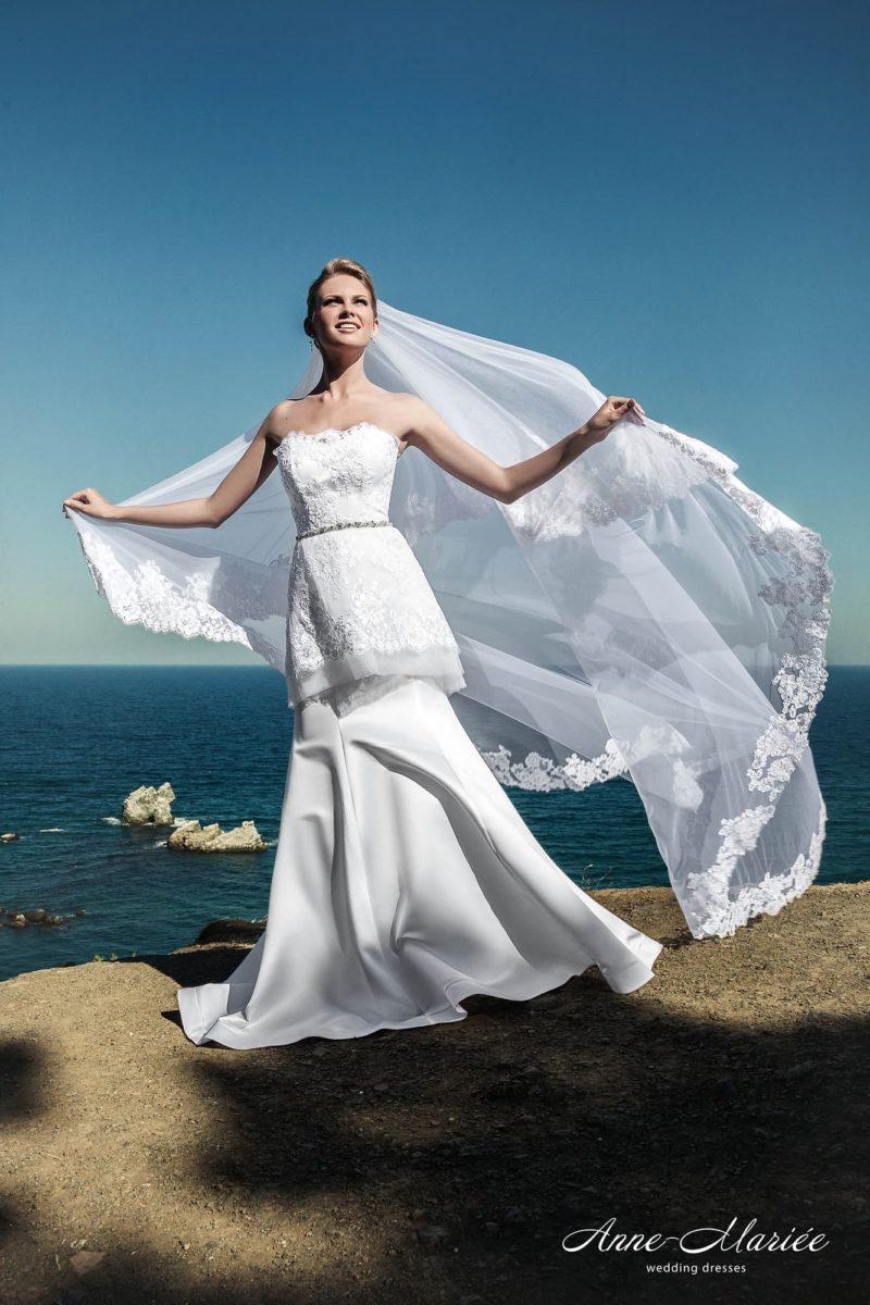 Открытое свадебное платье с длинной кружевной баской и узким серебристым поясом.