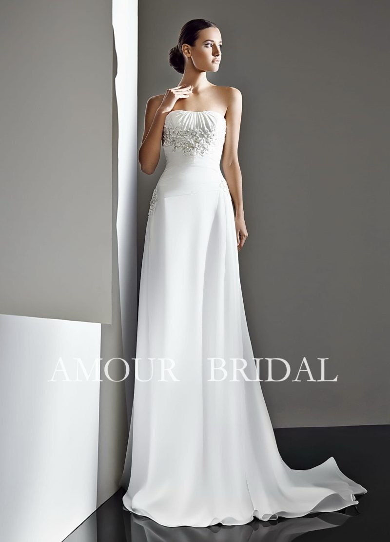 Прямое свадебное платье с длинным шлейфом и открытым лифом с вышивкой.