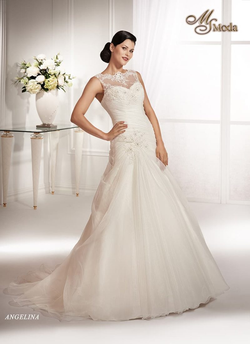 Закрытое свадебное платье силуэта «принцесса» с роскошными драпировками на талии.