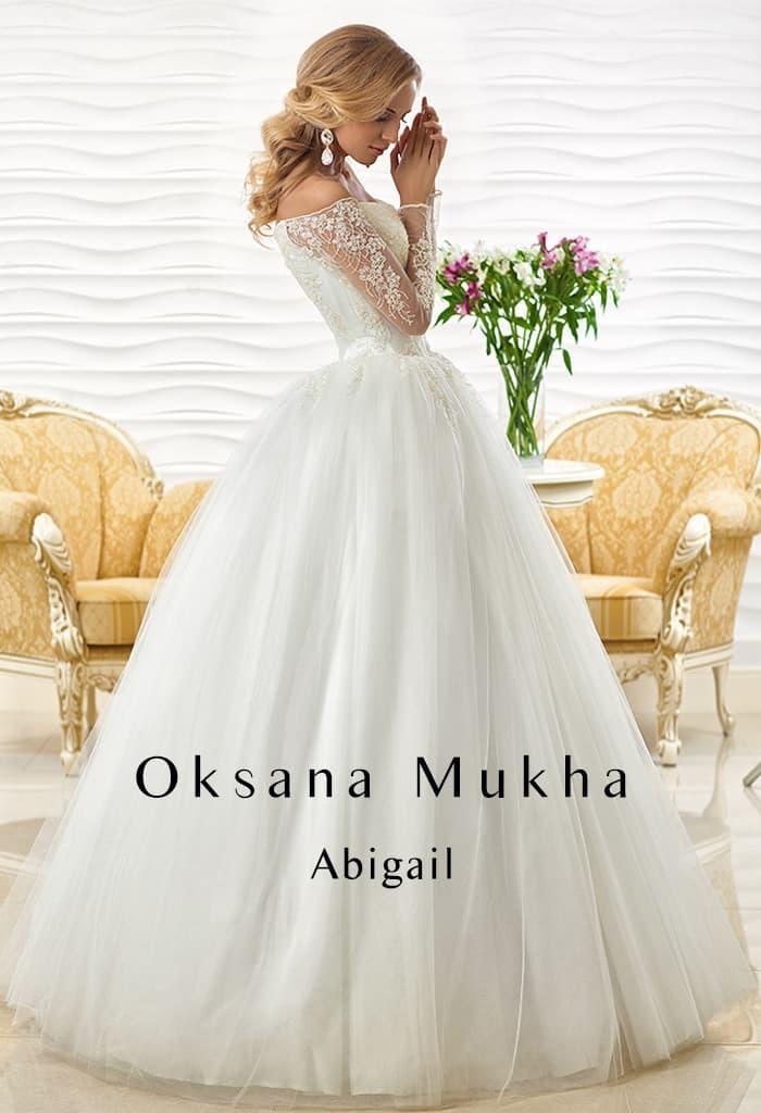 Свадебное платье с портретным декольте, дополненным длинным рукавом, и пышной юбкой.