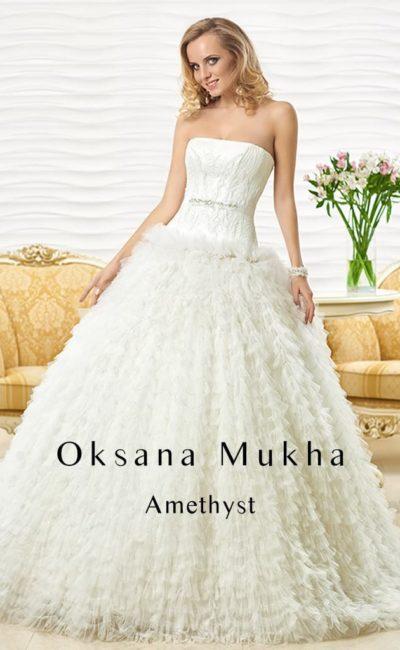 Пышное свадебное платье с фактурной отделкой многослойной юбки и украшенным бисером поясом.