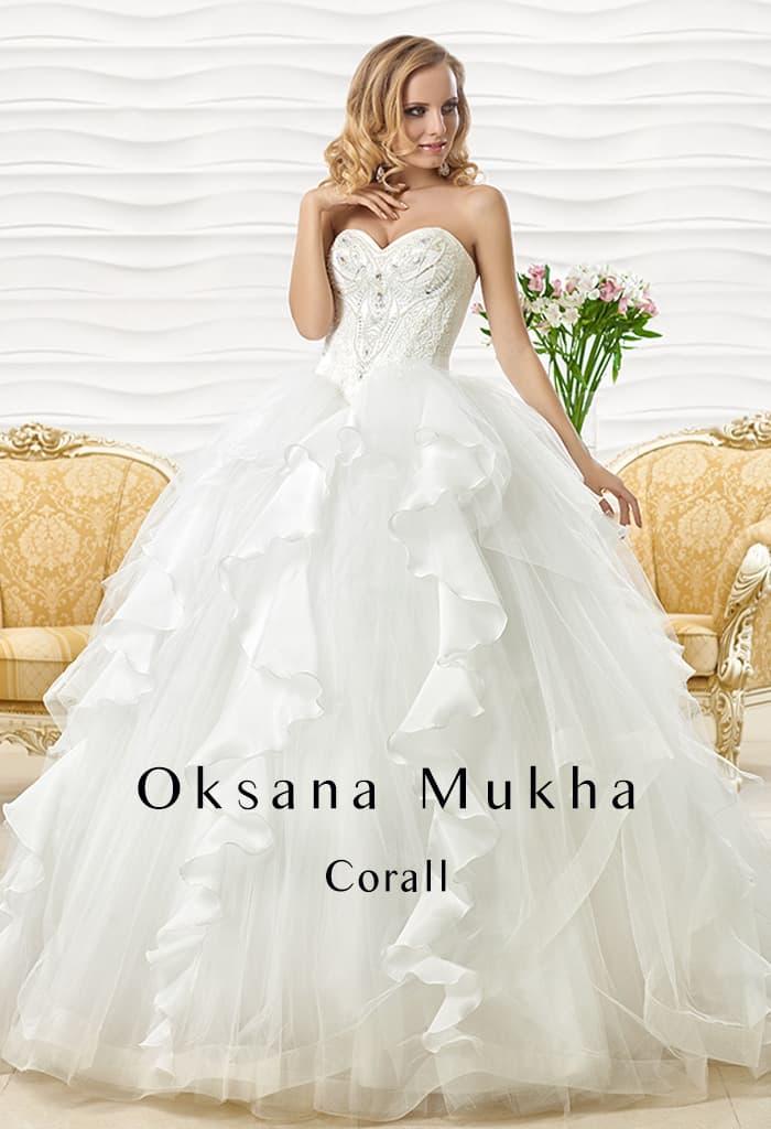 Свадебное платье с пышной юбкой, декорированной атласными оборками, и открытым лифом.