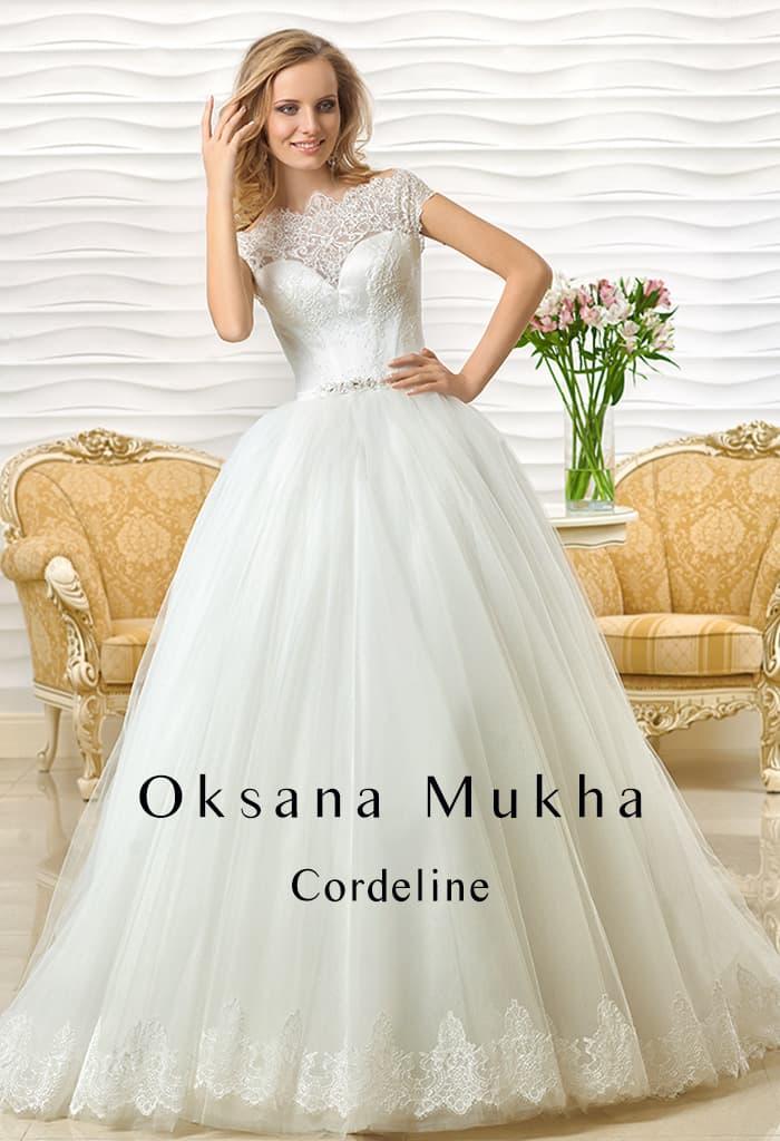 Пышное свадебное платье с атласным корсетом, покрытым кружевной тканью.