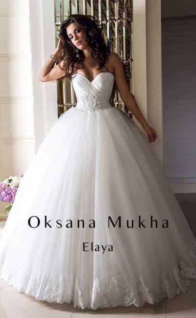 Пышное свадебное платье с открытым лифом с глубоким вырезом и драпировками на корсете.