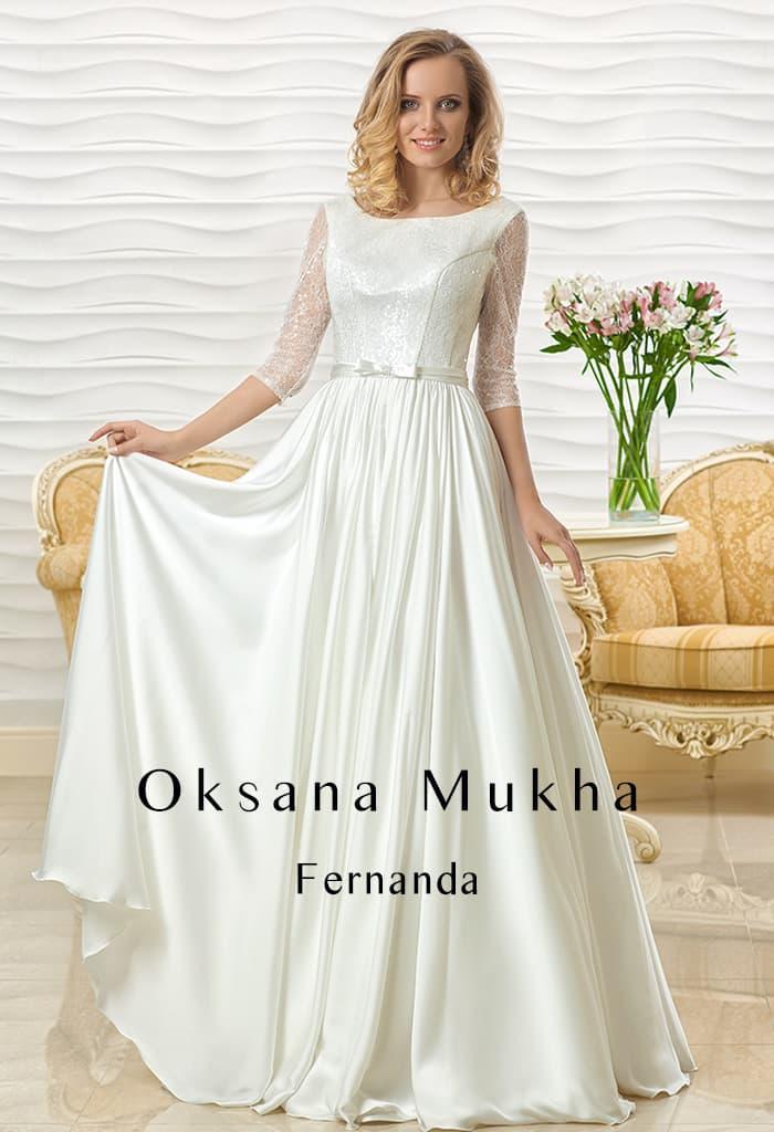 Атласное свадебное платье с прямым силуэтом и ажурными рукавами в три четверти.