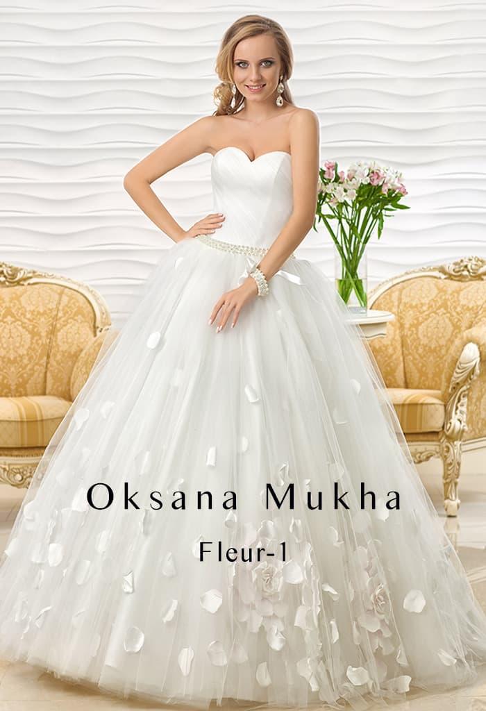 Свадебное платье с открытым лифом и пышной юбкой с декором из плотных лепестков.