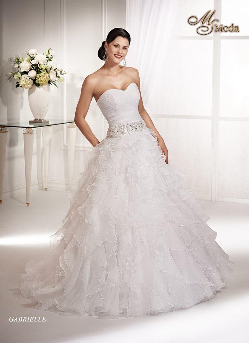 Открытое свадебное платье силуэта «принцесса» с полупрозрачными оборками на юбке.