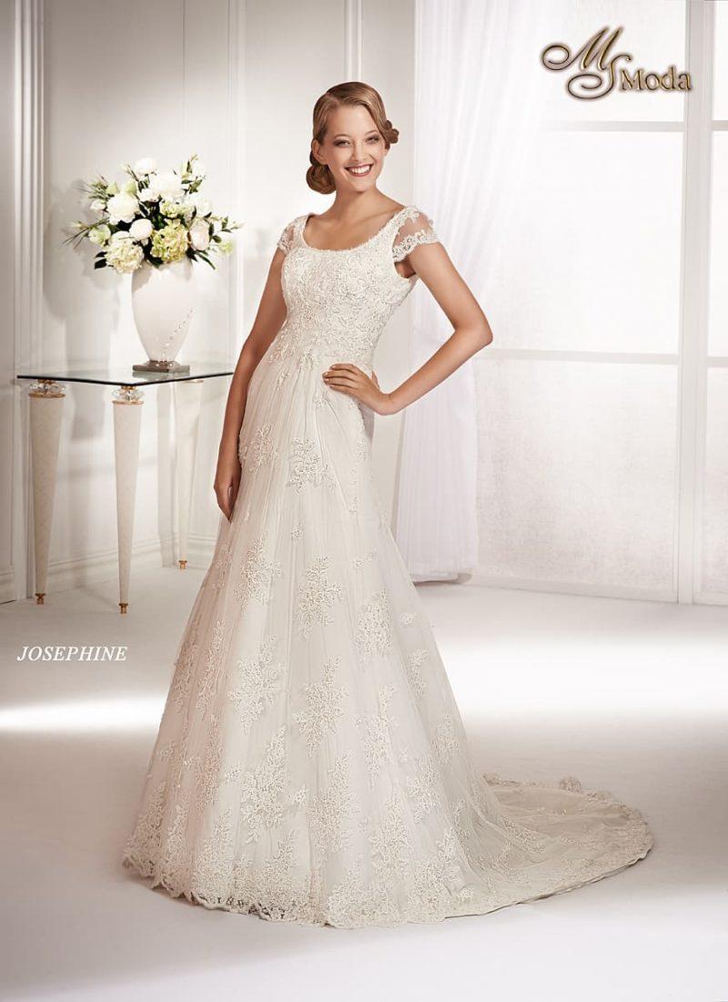 Кружевное свадебное платье прямого силуэта с длинным шлейфом и короткими рукавами.
