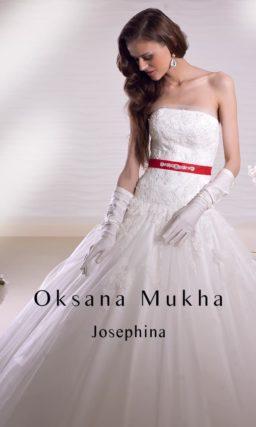 Пышное свадебное платье с кружевным корсетом и атласным поясом на талии.