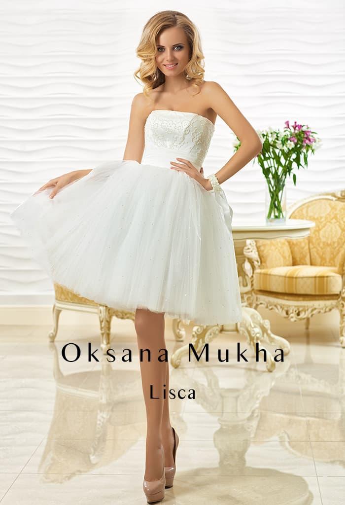 Короткое свадебное платье с юбкой, украшенной пайетками, и прямым вырезом декольте.