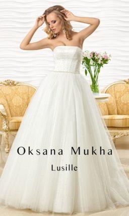 Пышное свадебное платье с воздушной многослойной юбкой и открытым лифом прямого кроя.