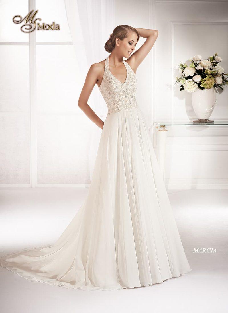 Изящное свадебное платье прямого силуэта с длинным шлейфом и V-образным лифом.