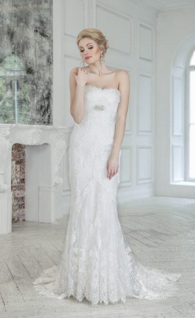 Прямое свадебное платье с завышенной линией талии и кружевным декором по всей длине.