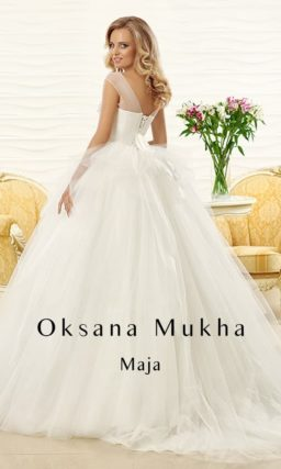 Пышное свадебное платье с полупрозрачным верхом, украшенным вышивкой.
