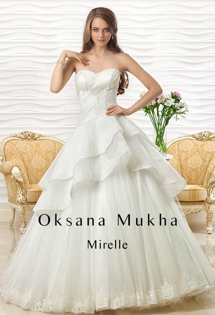 Открытое свадебное платье А-силуэта с пышными оборками ажурной ткани по юбке.