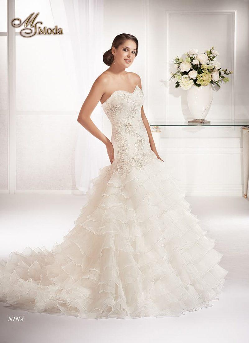 Кокетливое свадебное платье силуэта «рыбка» с оборками на юбке и небольшим шлейфом.