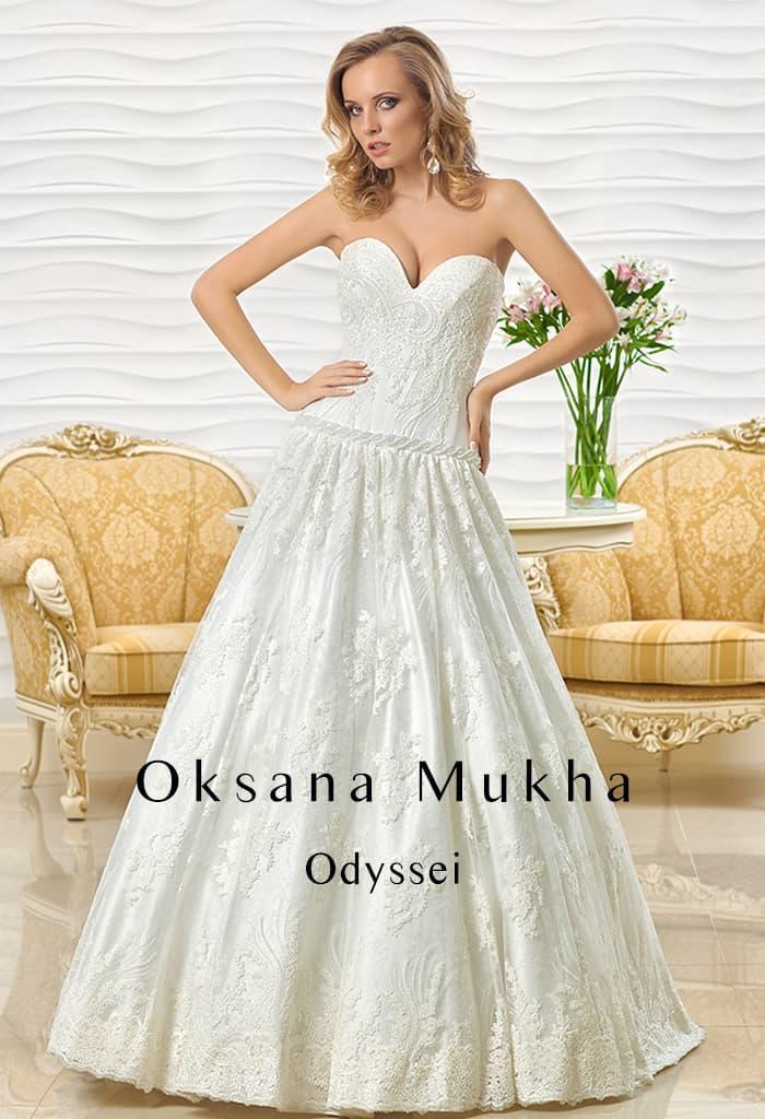 Свадебное платье с глубоким декольте сердечком и многослойной юбкой А-силуэта с кружевом.