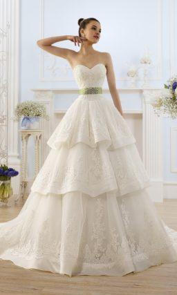Пышное свадебное платье с многоуровневой юбкой и широким цветным поясом.