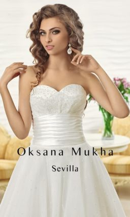Открытое свадебное платье с многослойной юбкой А-силуэта и широким атласным поясом.