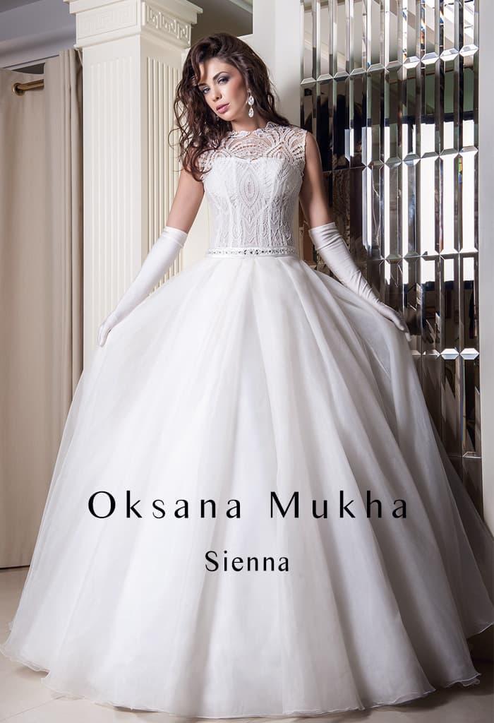 Пышное свадебное платье с закрытым верхом, оформленным плотной ажурной тканью.