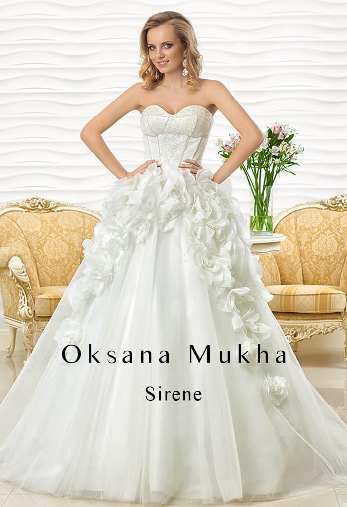 Пышное свадебное платье с объемными бутонами по верху подола и открытым корсетом.