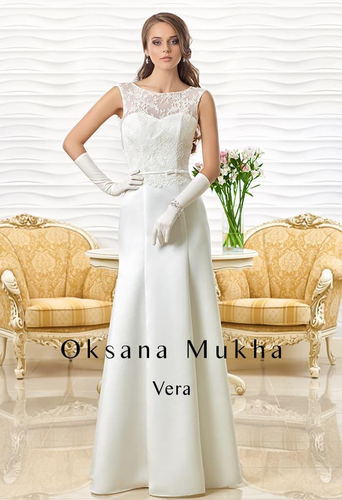 Прямое свадебное платье с кружевной отделкой открытого лифа и узким поясом.