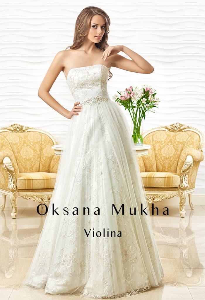 Прямое свадебное платье с кружевной отделкой и блестящим вышитым поясом на талии.