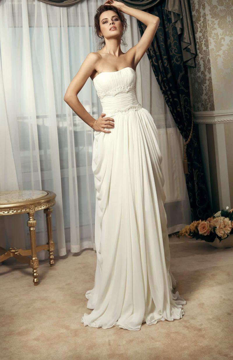 Ампирное свадебное платье с драпировками на юбке и открытым корсетом.