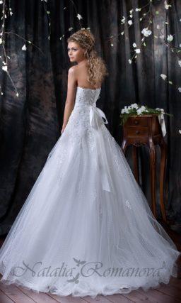 Пышное свадебное платье с ажурной многослойной юбкой и атласным поясом с бантом сзади.