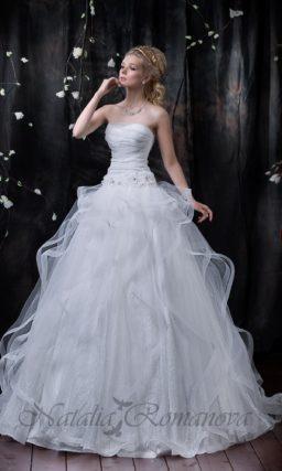 Открытое свадебное платье с полупрозрачными волнами ткани по пышной юбке.