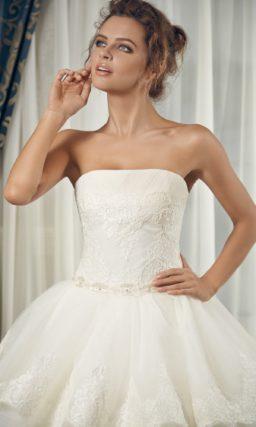 Пышное свадебное платье с открытым корсетом и многоярусной кружевной юбкой.