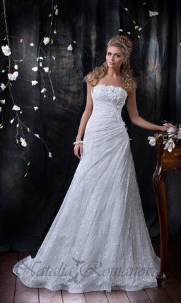 Кружевное свадебное платье с юбкой А-силуэта и прямым лифом, украшенным объемным декором.