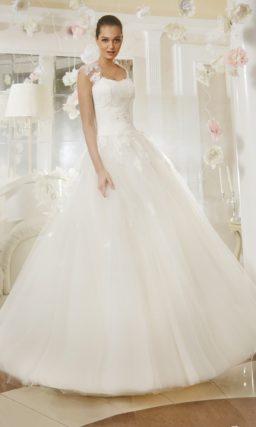 Пышное свадебное платье с прозрачными бретелями и вставкой на спинке, украшенными кружевом.
