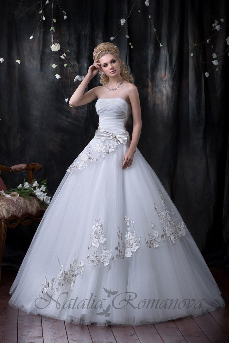 Открытое свадебное платье с прямой линией декольте и роскошным декором на пышной юбке.