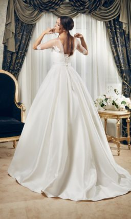 Пышное свадебное платье из атласной ткани, дополненное поясом и длинными рукавами.