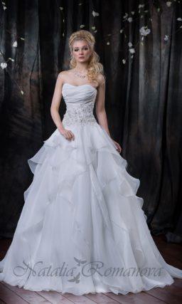 Открытое свадебное платье с торжественной юбкой, декорированной оборками из тонкой ткани.