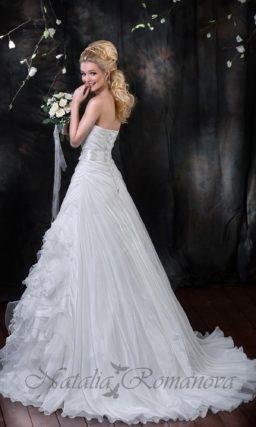 Атласное свадебное платье с пышным шлейфом и оборками по юбке А-силуэта.