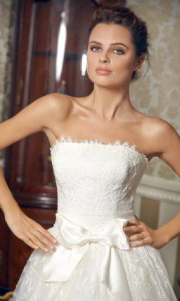 Свадебное платье длиной до середины икры с кружевным декором и широким поясом.