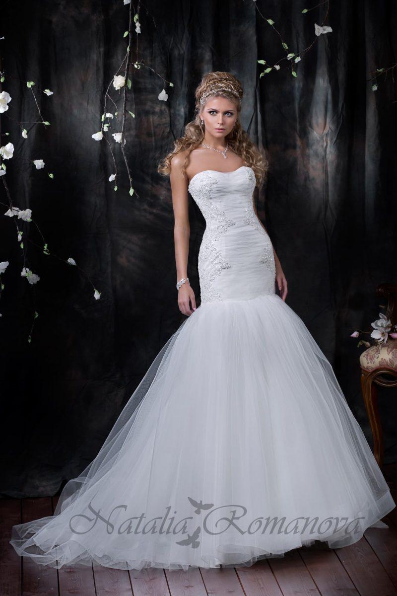 Открытое свадебное платье силуэта «рыбка» с многослойной юбкой и кружевом по бокам корсета.