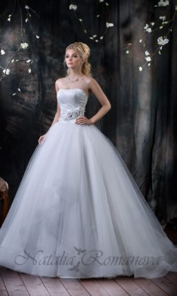 Свадебное платье пышного силуэта с оборками по подолу и открытым лифом с драпировками.