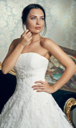 Пышное свадебное платье с лифом прямого кроя и кружевными аппликациями на юбке.